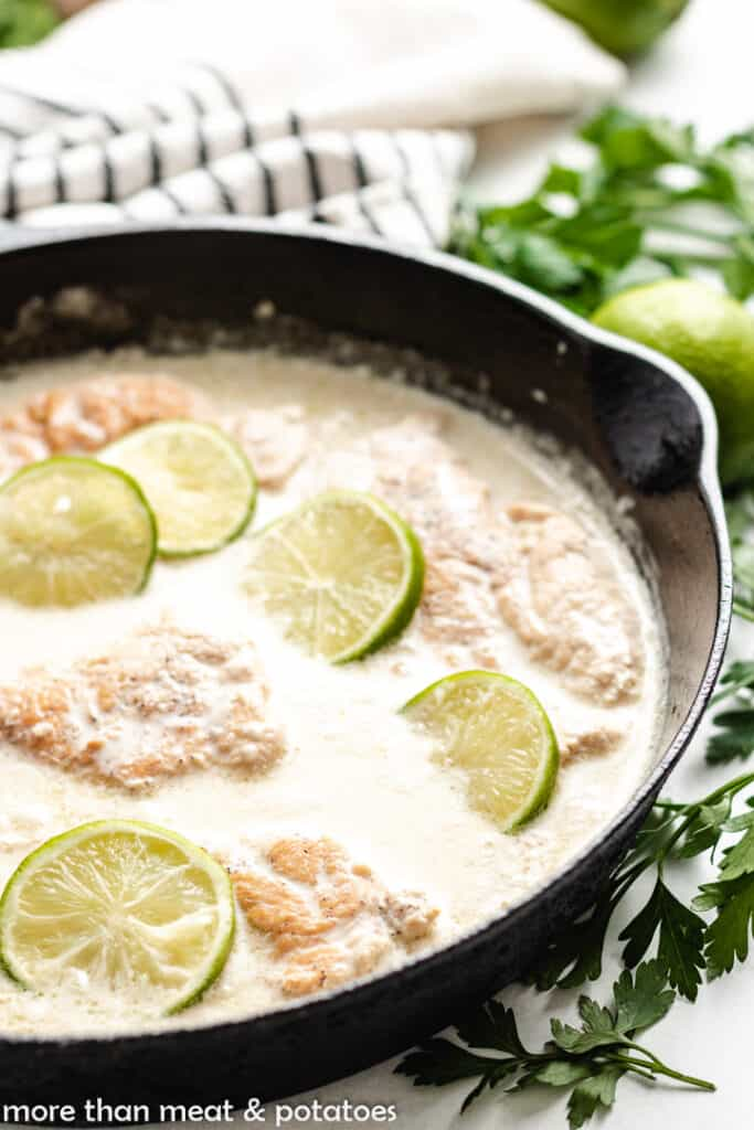 Chicken cutlets cooking in a coconut sauce.