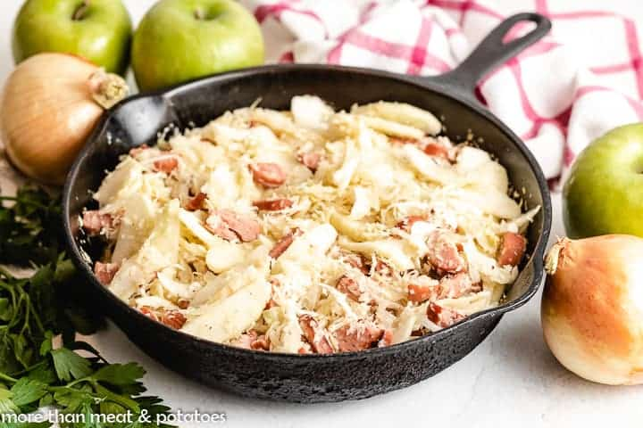 The cooked sausage and cabbage in a skillet.