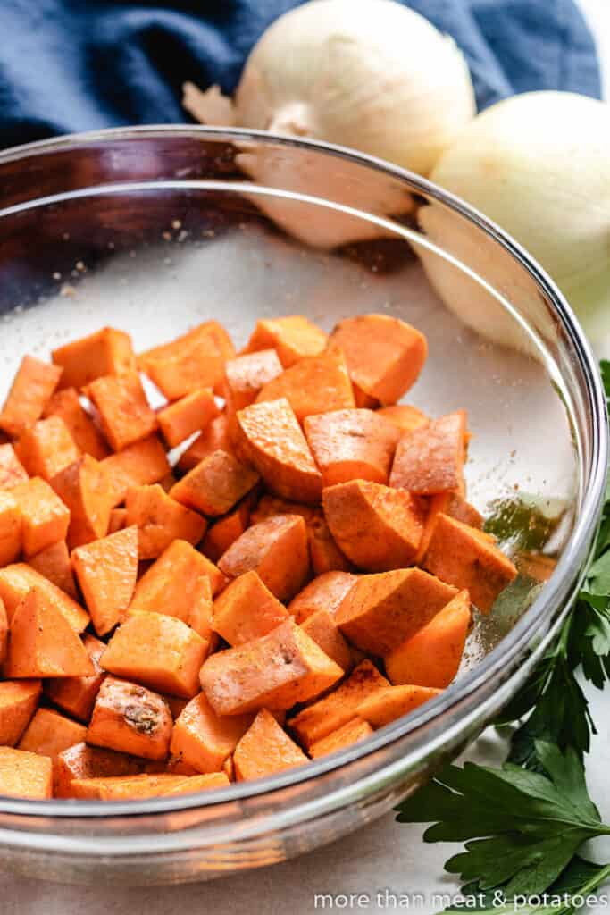 Diced sweet potatoes tossed with avocado oil in a bowl.