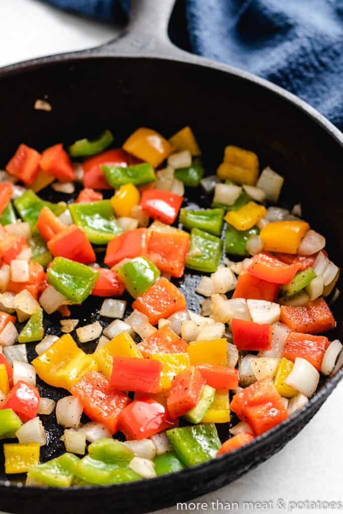 Diced peppers and onions cooking in the skillet.