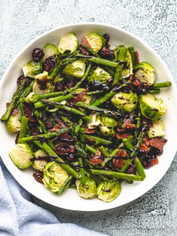 The roasted asparagus and brussel sprouts in a bowl.