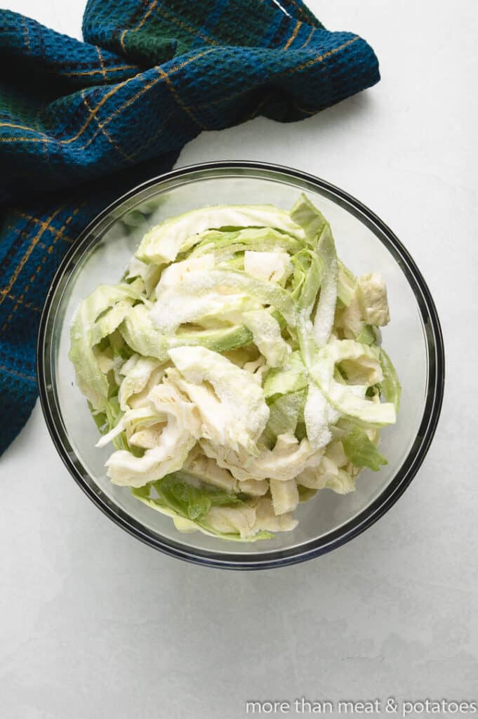 Chopped and uncooked cabbage in a mixing bowl.