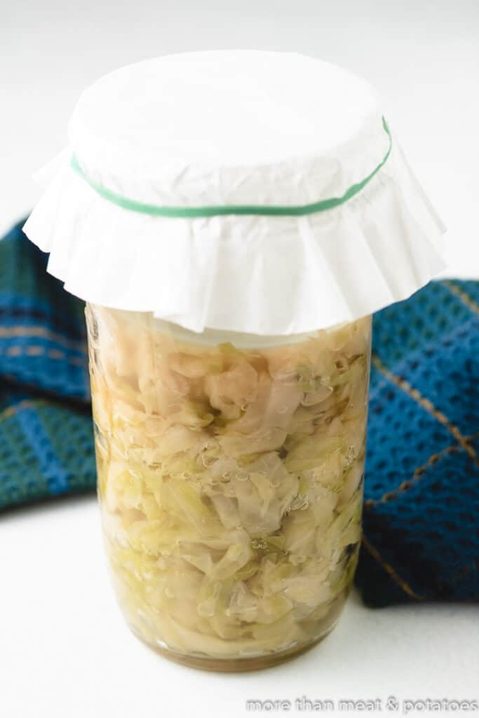 The cabbage changes color while fermenting in the jar.