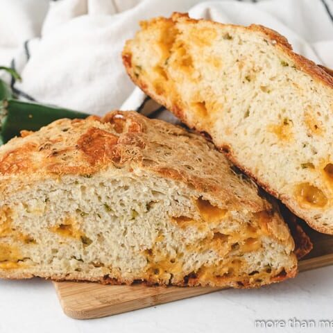 A sliced and stacked loaf of jalapeno cheese bread.