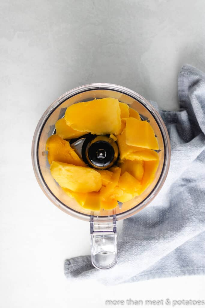 Chunks of mango in a food processor.