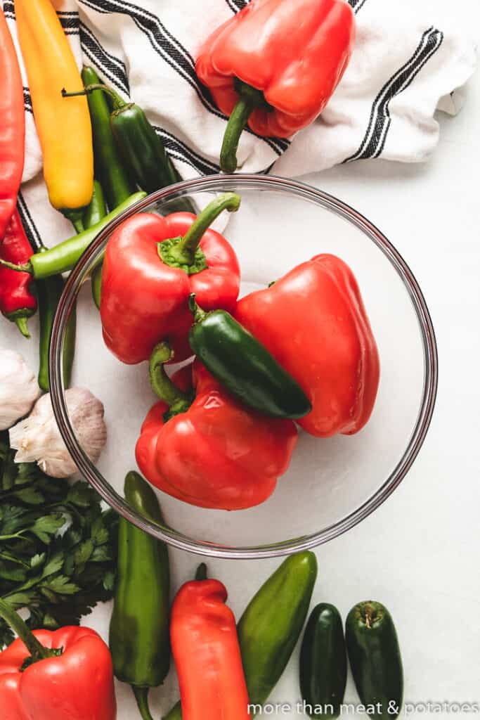 Fresh bell peppers and a jalapeno in a bowl.