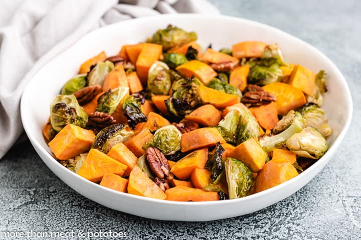 A bowl of roasted brussel sprouts and sweet potatoes.