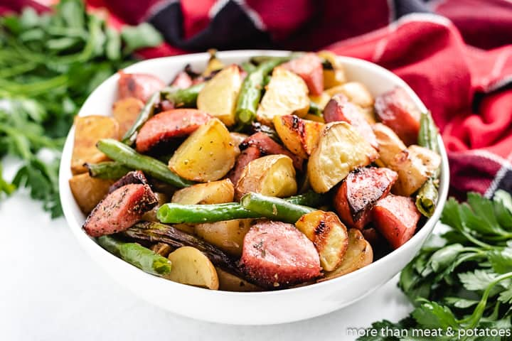 A bowl filled with sausage green beans and potatoes.