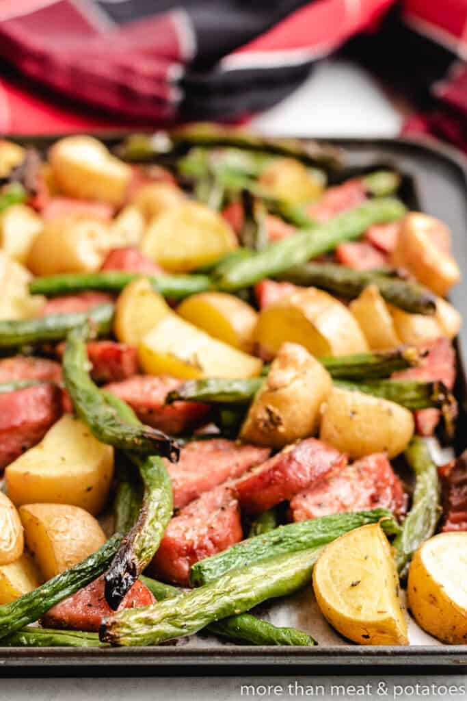 An up-close view of the sausage and veggies on a pan.