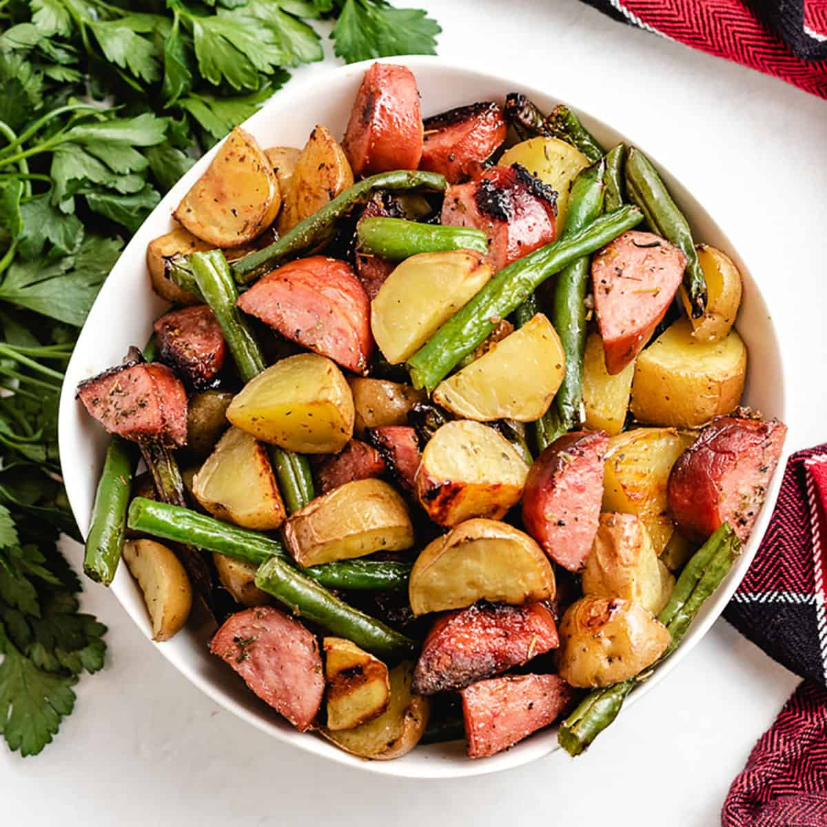 The cooked sausage green beans and potatoes in a bowl.