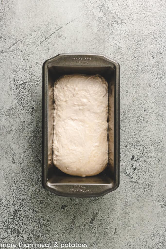 The dough transferred to the loaf pan to rise.