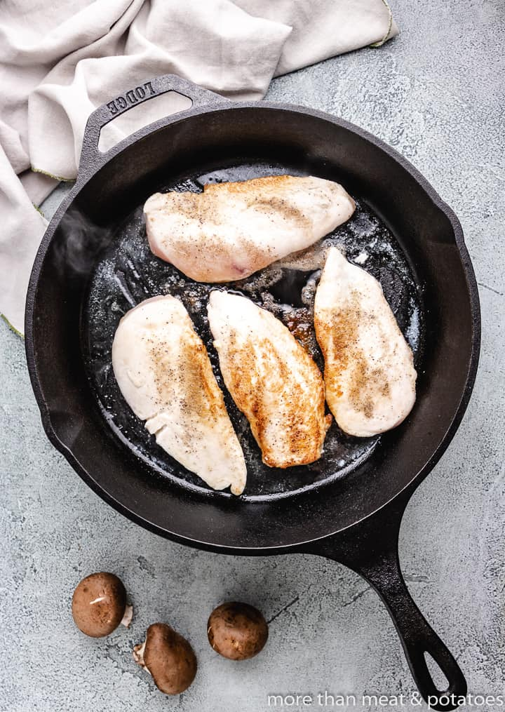 The chicken breasts cooking in a skillet.