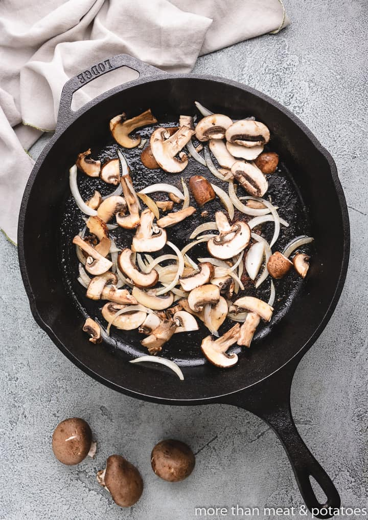 Mushrooms and onions sauteing in a skillet.