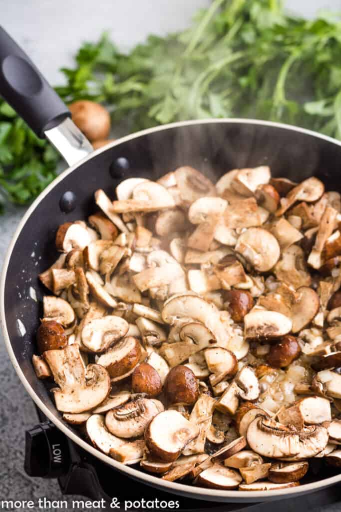 Sliced mushrooms and onions cooking in a saucepan.
