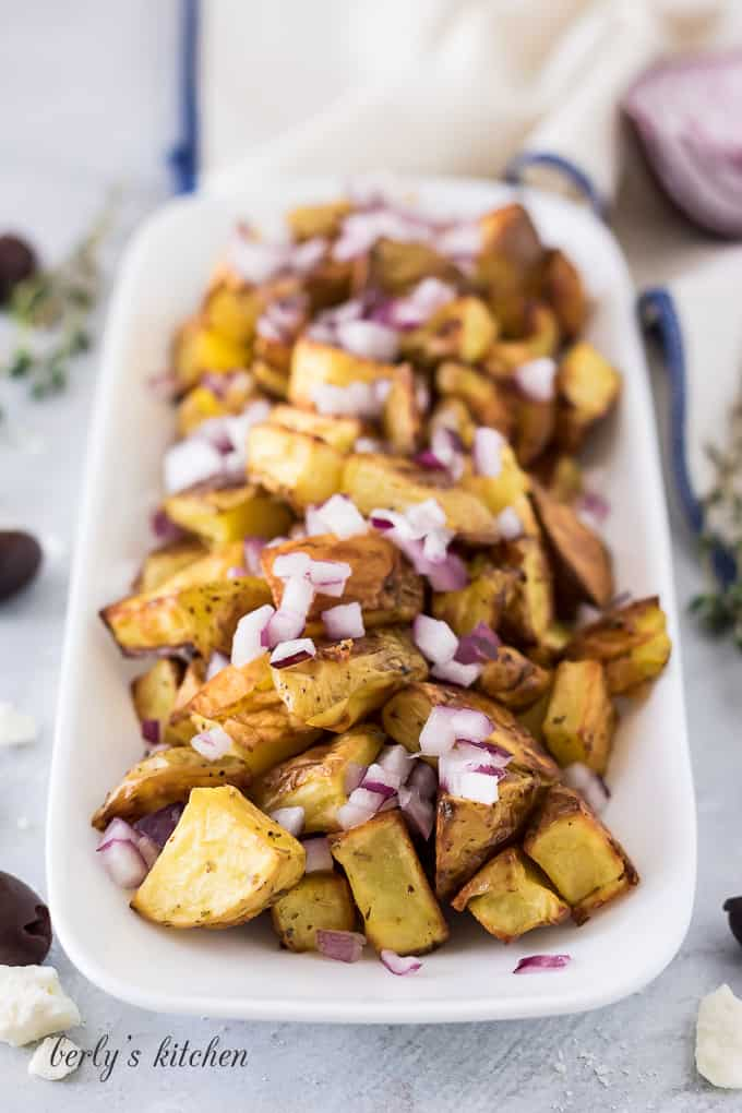 Roasted potatoes topped with diced red onion.