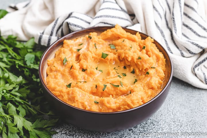 Savory mashed sweet potatoes served in a ceramic bowl.