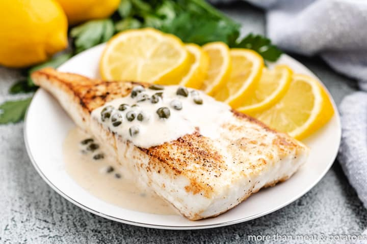Pan seared halibut garnished with fresh lemon.