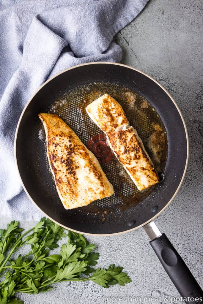 The halibut searing in a hot pan.