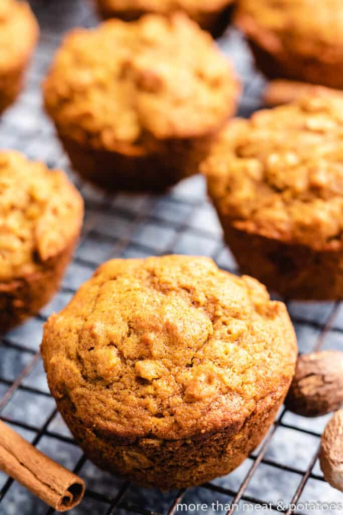 The oat muffins sitting on a black rack.
