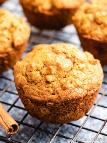 Four pumpkin oatmeal muffins on a cooling rack.