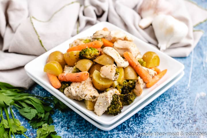 The sheet pan chicken and veggies on a square plate.