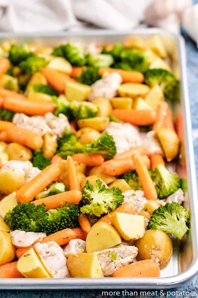 Raw chicken and vegetables on a lined sheet pan.