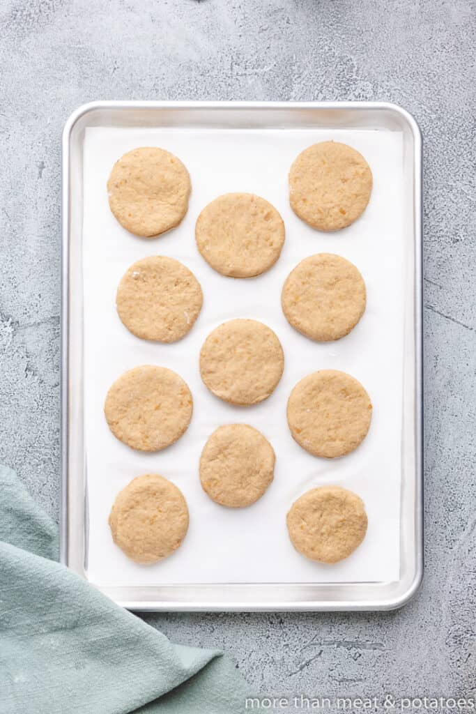 The raw biscuits sitting on a lined sheet pan.
