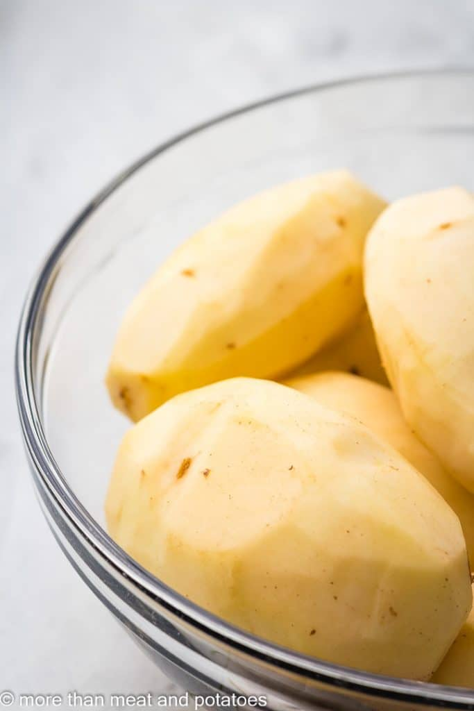 Peeled potatoes in a mixing bowl.