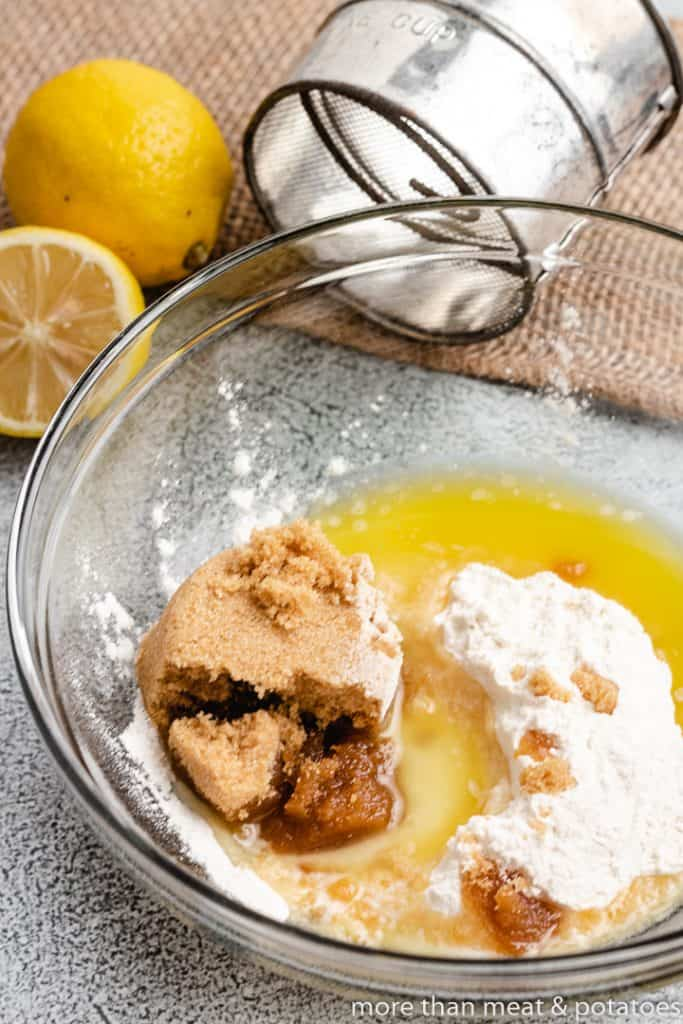 Flour, brown sugar, and melted butter in a bowl.