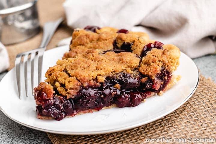 A slice of cherry pie with crumb topping on a plate.
