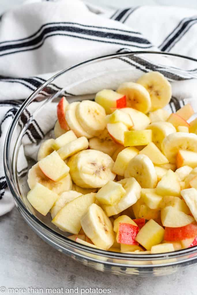 Sliced bananas and apples in a mixing bowl.
