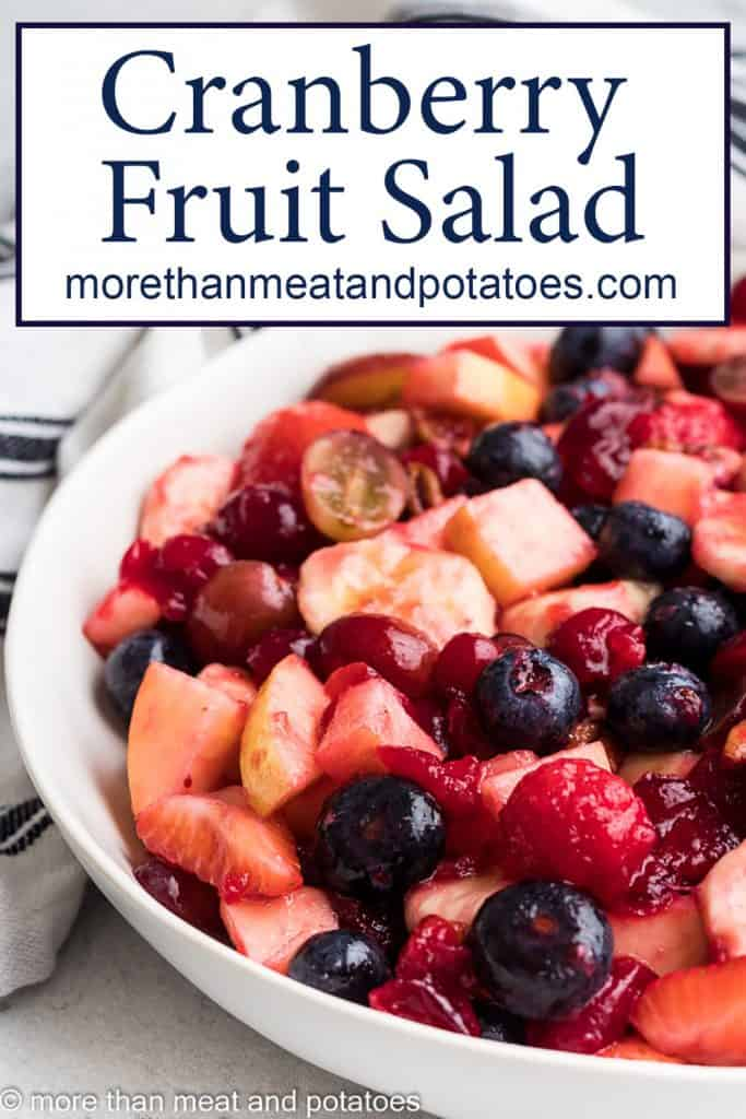 A fruit salad tossed with a cranberry syrup.
