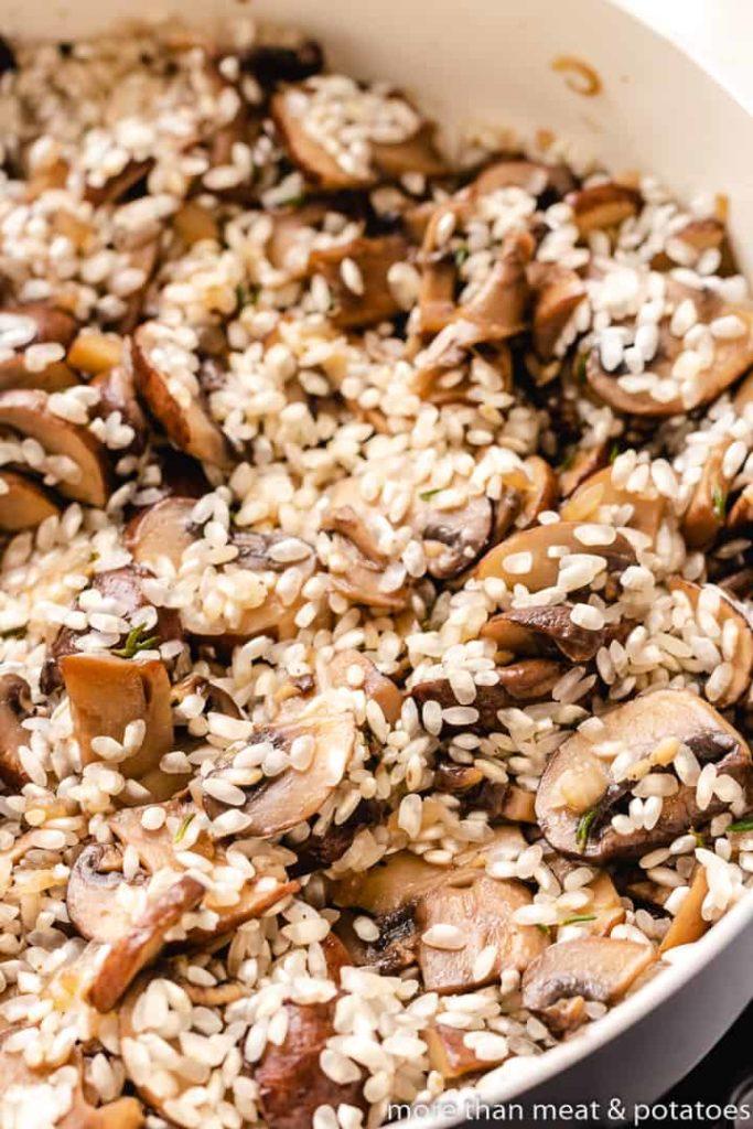 Dry Arborio rice added to the mushrooms.