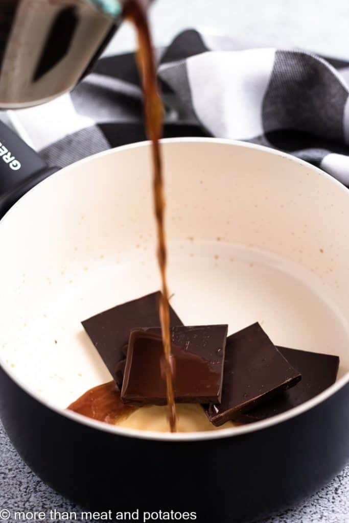 Hot coffee being poured over chocolate squares.