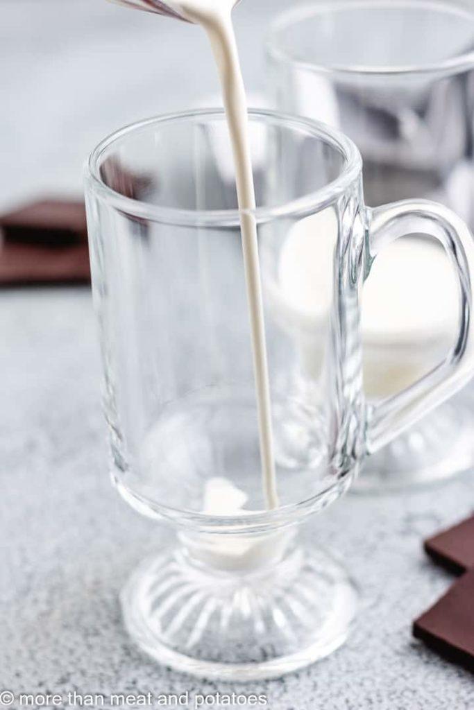 Heavy cream being poured into a glass mug.