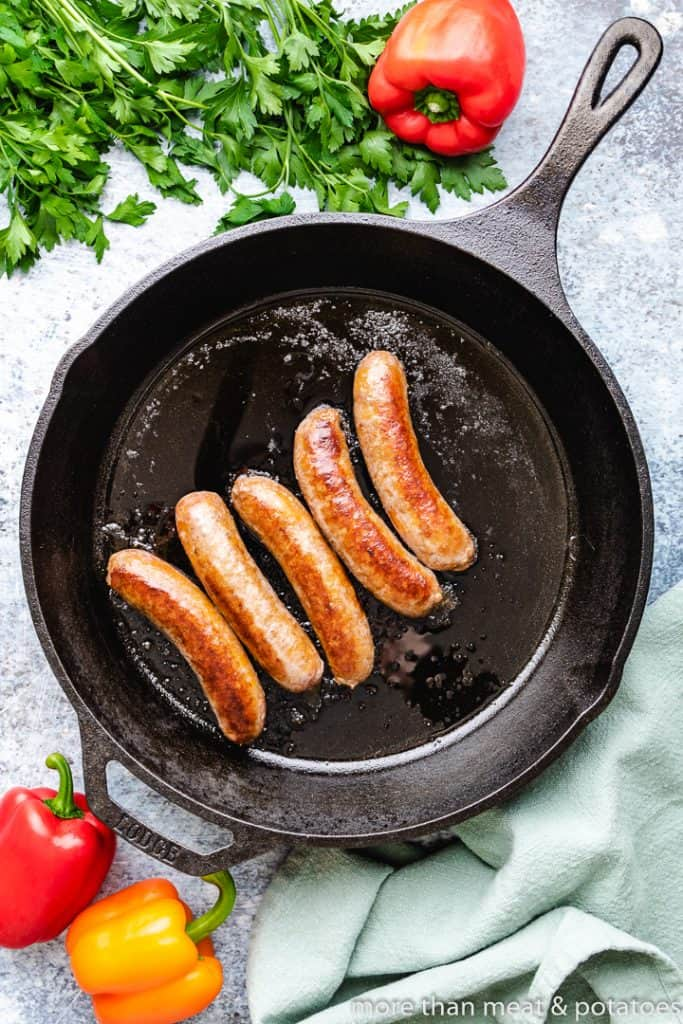 Five sausage links cooking in a skillet.