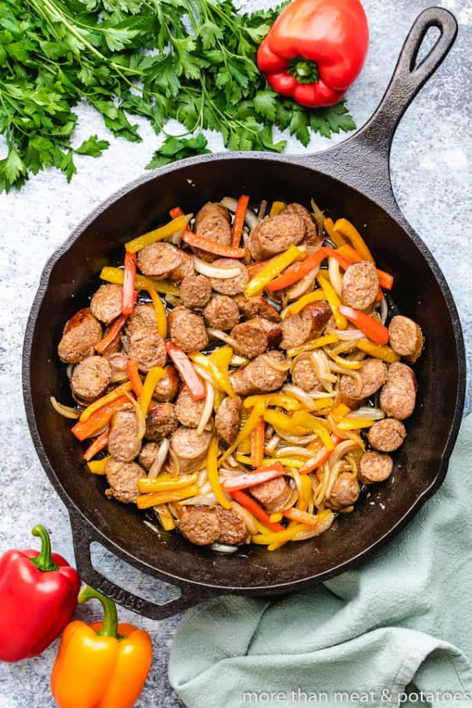 The meat, peppers, and onions cooking in the skillet.