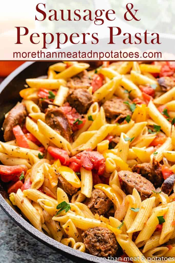 The finished sausage and peppers pasta in a skillet.