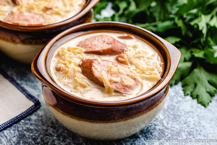 Sausage and sauerkraut soup served in earthenware bowls.