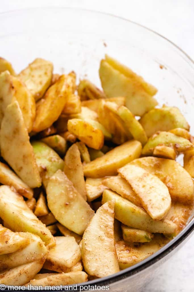 The apples tossed with sugar and other ingredients.