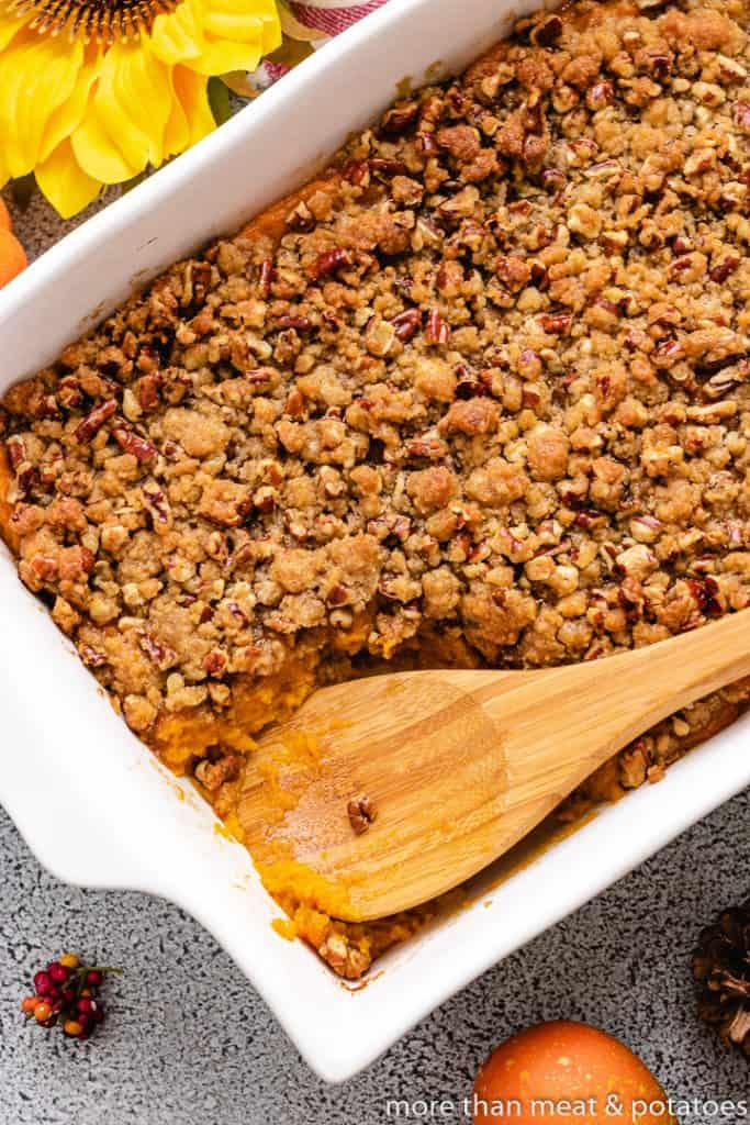The sweet potato casserole with pecans a wooden spoon.