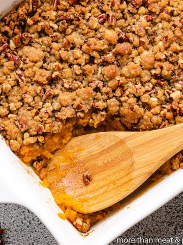 Baked sweet potato casserole with pecan streusel in a dish.