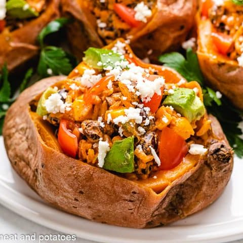 Four black bean stuffed sweet potatoes on a plate.
