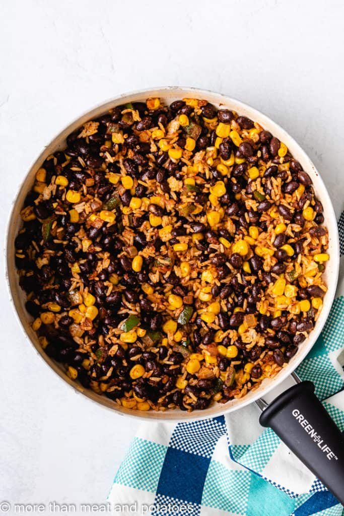 Black beans, corn, and other ingredients added to the skillet.