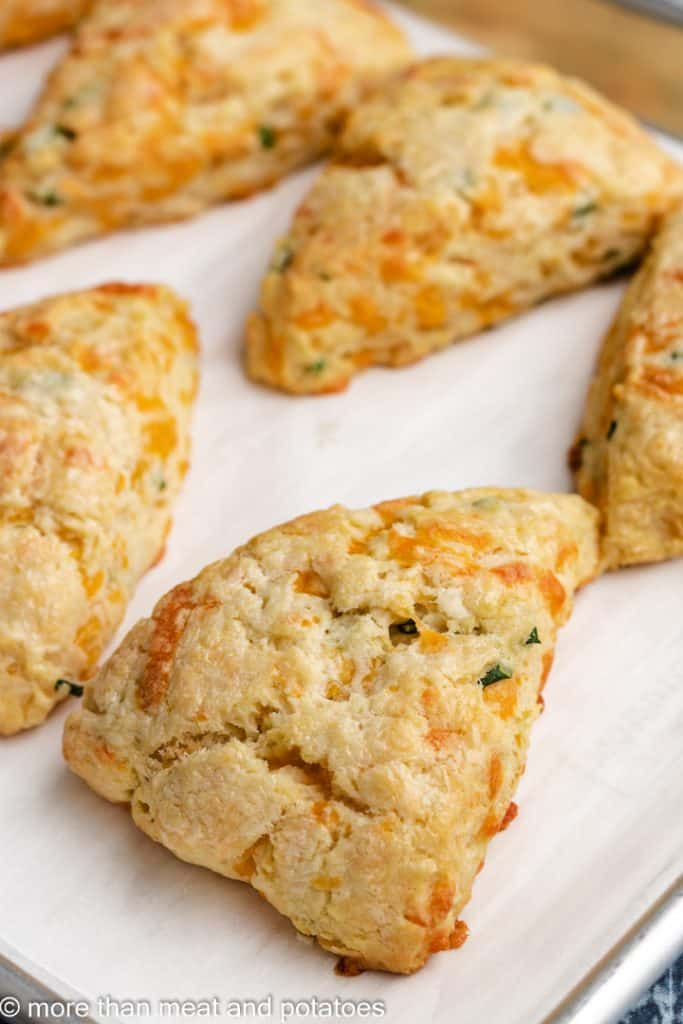 Five cheesy scones on the lined sheet pan.