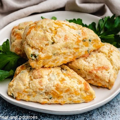 Four cheddar chive scones stacked on a plate.