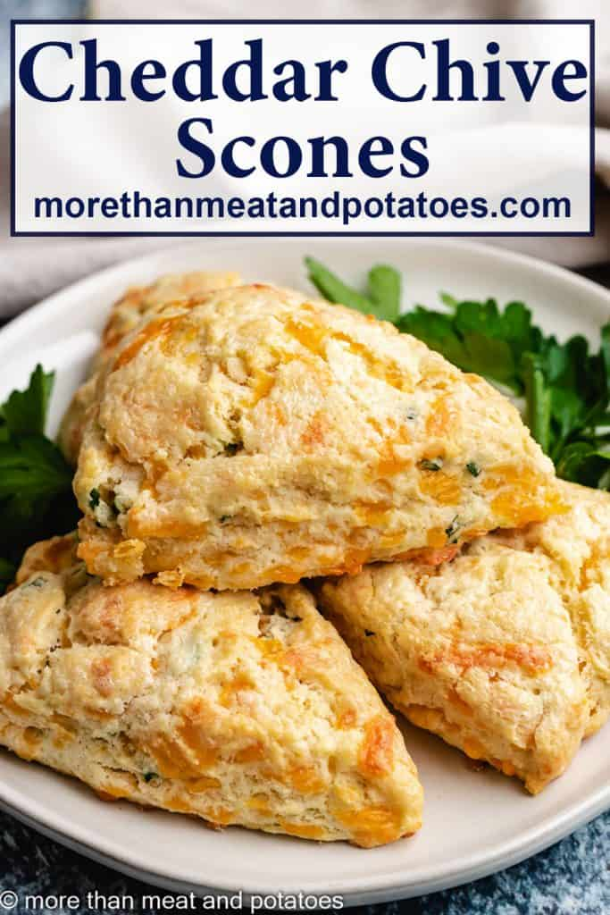 Cheddar chives scones served on a white plate.