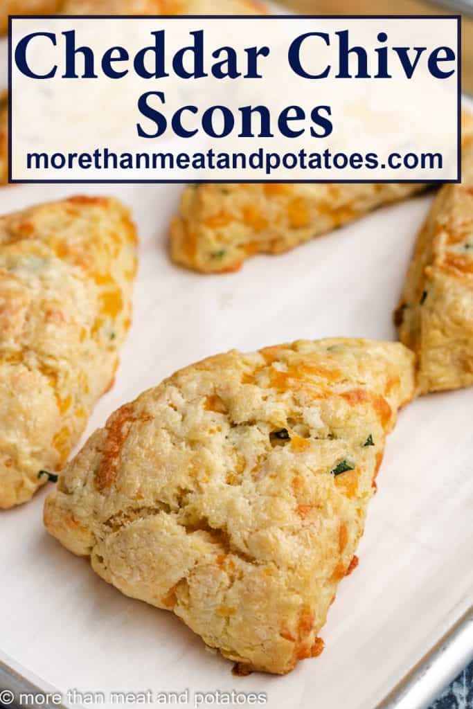 Cheddar chive scones on a sheet pan lined with parchment paper.