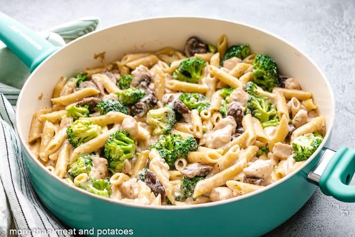 Chicken mushroom broccoli pasta in a blue skillet.