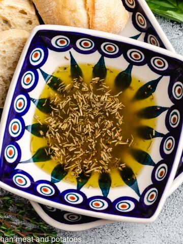 The bread dipping oil in a decorative bowl.